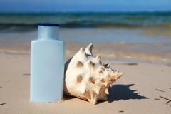 Sun protection cream with white cockshell Stock Photos