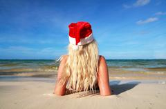 Stock Photo of woman in santa hat on beach