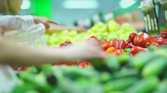 Customers select cucumbers, paprika peppers and tomatoes in supermarket - stock footage