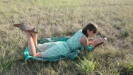 Stock Video Footage of Young woman browsing in Internet with tablet lying on the grass