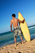 Surfer holding a surfboard Stock Photos