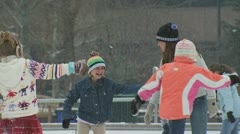 A woman skating at a ice rink with a young girl and her friends Stock Footage