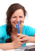 happy girl with pens and pencils in hands - stock photo