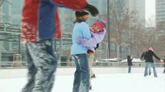 A woman and a young girl playing at a busy ice rink Stock Footage