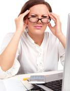 tired businesswoman holding her head - stock photo