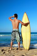 surfer holding a surf board - stock photo