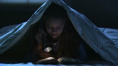 Girl reading under the covers Stock Footage