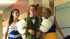 Nerd walking with two cheerleaders Stock Footage