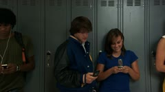 Panning shot of high school students on cell phones Stock Footage