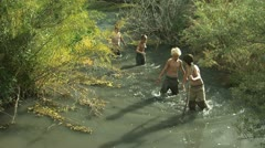 Four boys hiking up a river Stock Footage
