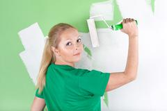 young woman with paint roller in hand - stock photo