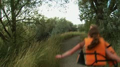 Two girls skipping down a trail with life vests Stock Footage