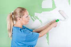woman with paint roller in hands - stock photo