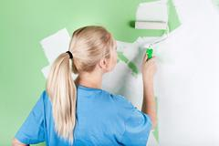 young woman paints the wall - stock photo