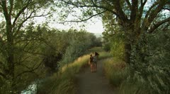 mother and daughter walking down a trail - stock footage