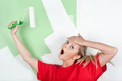 Shocked woman with paint roller in hand Stock Photos