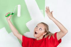 happy woman in red t-shirt with paint roller in hand - stock photo