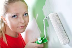 woman with paint roller in hand - stock photo
