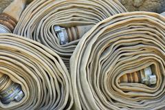 Old rolled fire hoses with nozzles Stock Photos