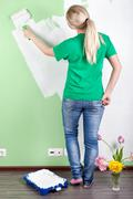 portrait of  a girl painting the wall - stock photo