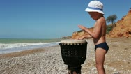 Stock Video Footage of Little Boy Funny Playing Ethnic African Djembe Drum on the Lonely Wild Beach