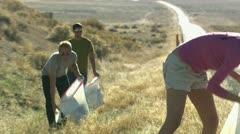 three people picking up trash on the side of the road - stock footage