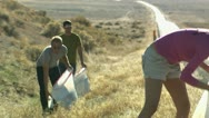 Stock Video Footage of three people picking up trash on the side of the road