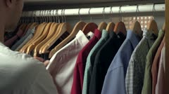 Man picking out a shirt to wear from his closet Stock Footage