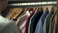 Stock Video Footage of Man picking out a shirt to wear from his closet