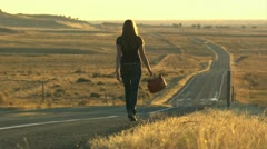 Woman walking down the road with a gas can Stock Footage