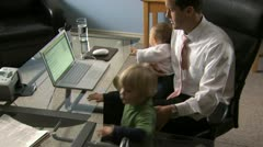 Man with two children looking at a notebook computer Stock Footage
