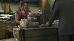 Stock Video Footage of grocery clerk bagging groceries in a reusable bag