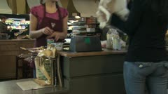 Grocery clerk bagging groceries in a reusable bag Stock Footage
