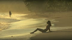 Woman sitting in the surf Stock Footage