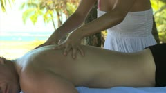 woman giving a man a massage under palm trees - stock footage