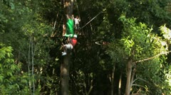 Two people passing each other on zip lines through the trees Stock Footage