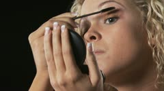 Young woman putting on mascara Stock Footage