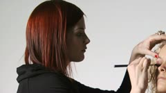 Makeup artist applying makeup to a woman Stock Footage