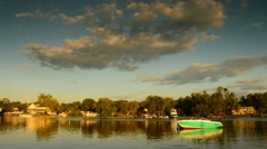 Timelapse of Evening Sky, lake, homes along river bank and rolling clouds time l Stock Footage
