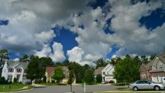 Time lapse of idyllic suburbs with homes on a cul de sac and rolling cumulus clo - stock footage