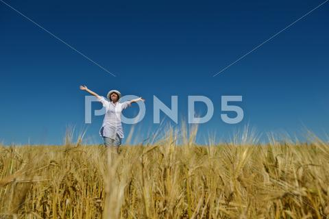 Stock photo of young woman in wheat field at summer