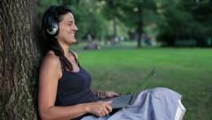 Stock Video Footage of Happy woman watching movie on laptop in the park, crane shot HD