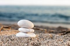 stack or pile of balancing stones on sea beach - stock photo