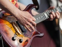 Human hand holding guitar music instrument Stock Photos