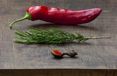 Fresh red pepper, sprig of rosemary, wooden spoon of red pepper - stock photo