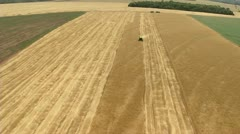 Aerial view of agricultural area with combine harvester Stock Footage