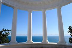 Ancient Greek columns against a blue sky and sea Stock Photos