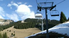 Ski lift rising over spring slopes 	  8915. Stock Footage