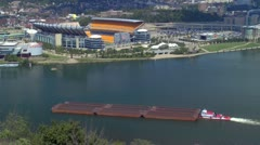 Barge passing Heinz stadium on Ohio river in Pittsburg Stock Footage