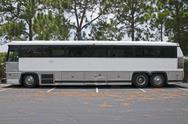 Stock Photo of retired tour bus with tinted windows waiting to be sold